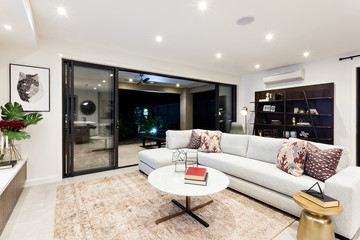Modern living area with outside patio view at night