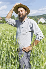 Young farmer with hat standing in the wheat