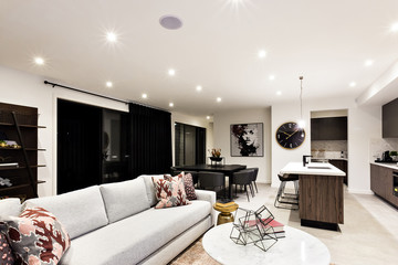 Luxury living room with sofas and pillows beside kitchen