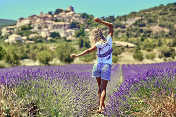 Blonde girl in a wide field of lavender. Young woman walking in purple lavender flowers. On the...