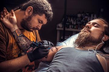 Professional tattooer works in tattoo parlor