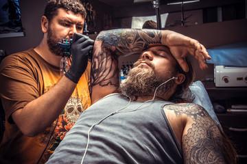 Tattooer working tattooing in tattoo parlor