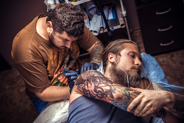 Professional tattooist at work in tattoo studio