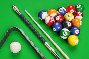 Group of billiard colored balls, cues and triangle on green tabl