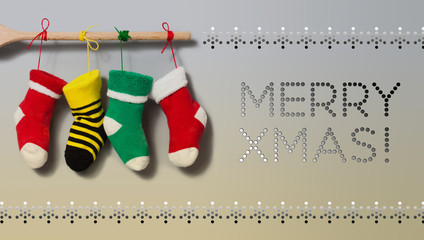 Merry Xmas text invitation card. Hanging Christmas socks on gradient gray beige background. Colorful stocking decoration poster. Wooden plank and colored ropes, snowflakes