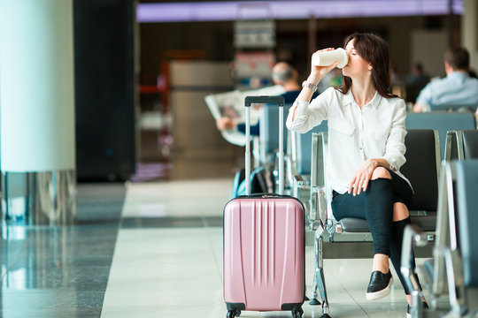 Airline passenger in an airport lounge drinking coffee and waiting for flight aircraft. Caucasian woman with glasss if hot coffee in the waiting room