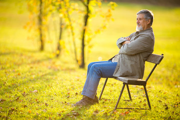 Portrait of a senior man outdoors, sitting on a bench in a park