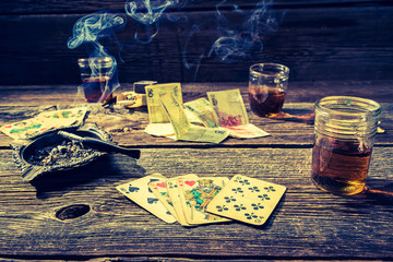 Old illegal gambling table with vodka, cigarettes and cards