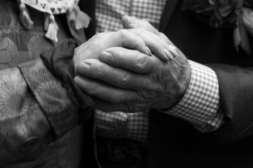 Elderly man and an elderly woman holding hands.Black and white