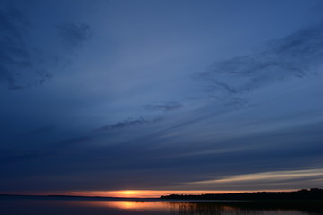 Dark blue sky at sunset over the lake in the summer evening
