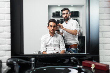 the hairstylist is brushing the client's hair in barbershop