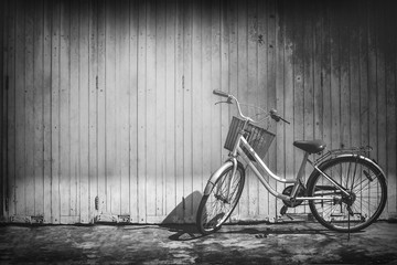 vintage bicycle on vintage wooden house wall,black and white picture