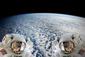 High resolution planet Earth two astronauts spaceman helmet suit floating people outer space walk. Elements of this image furnished by NASA.