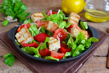 Vegetable salad with romano, tomatoes, peas and croutons on a co