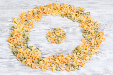 Pasta lined with a circle on wooden background, view from the top