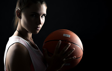 portrait of a beautiful and sexy girl with a basketball in studio