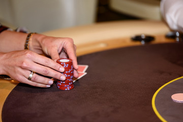 Closeup of hands with chips on poker table, selective focus