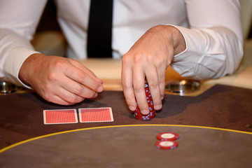 Closeup of hands of poker player with chips on poker table, sele