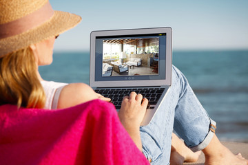 Working on the beach. Mature woman using laptop at seaside.