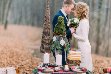 Happy young wedding couple softly holding hands near the decorated table for Christmas holidays in autumn forest.