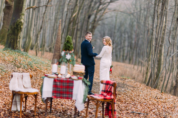 Happy young wedding couple walking and holding hands near the decorated table for Christmas holidays in autumn forest.