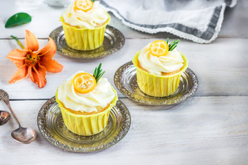 Cupcakes with cream cheese on white wooden table.