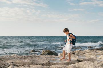 Liittle boy on a rock in sea waves