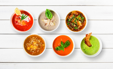 Variety of soups at white wood, top view