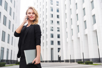 Attractive blonde businesswoman with phone and laptop on urban backgroud