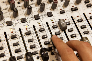 Professional audio mixing console with faders and adjusting knobs