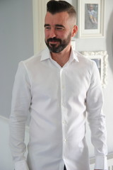 An englishman with a beard wearing a white shirt