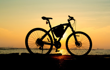 Silhouette of mountain bike at sea with sunset sky background