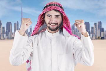 Arabian man expressing his success outdoors