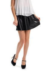 Girl in short black skirt. Dark heels and white top. Model wears designer shoes. Quality clothes and exclusive footwear.