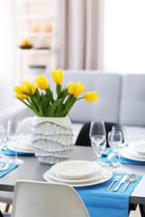 Table served with dishes and a bouquet of tulips