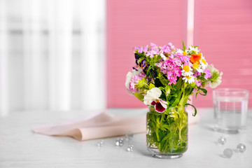 Meadow flowers bouquet in glass vase on table