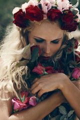Retro vintage style portrait of beautiful blonde woman with rose
