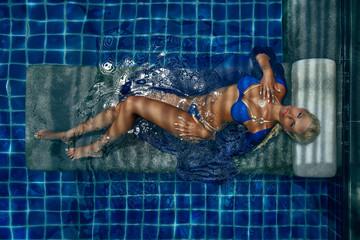 fashion photo of sexy beautiful girl in blue bikini relaxing in