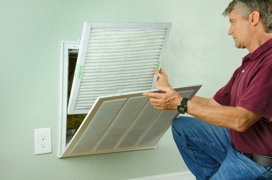 Professional repair service man or diy home owner a clean new air filter on a house air conditioner which is an important part of preventive maintenance.