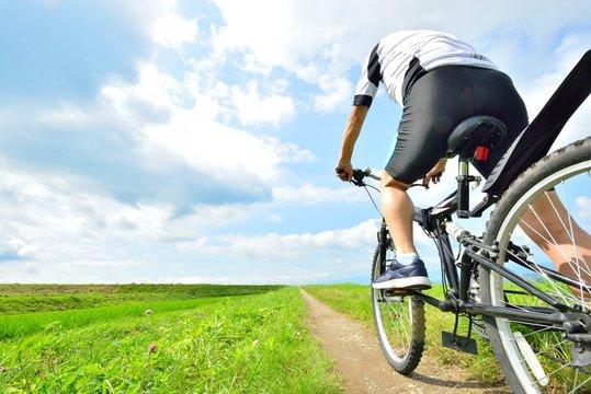大空と田園の風景をマウンテンバイクで走る