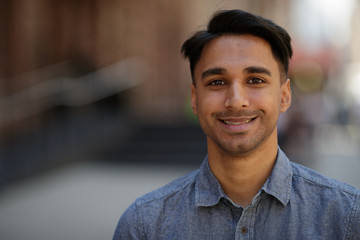 Young Indian man in city face portrait smile