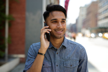 Young Indian man in city talking on cell phone