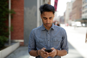 Young Indian man in city texting cell phone