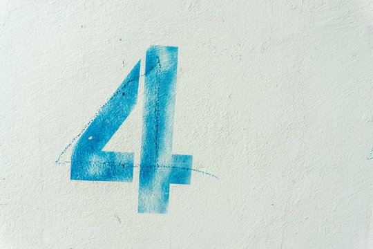 the number 4 on the dirty white wall