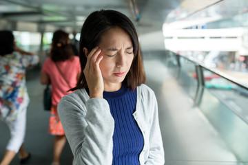 Woman feeling headache in the foot bridge