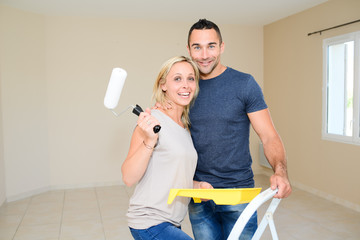 happy young couple renovating and painting and moving into their new house