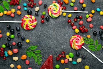 Swirling colorful lollipops with candy on black background