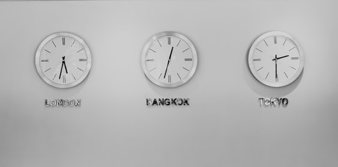Black and white London, Bangkok and Tokyo watches hanging on the wall