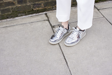 Woman standing in street wearing silver shoes, detail