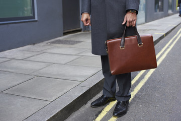 Man standing in street holding brown briefcase, low section